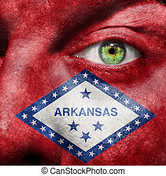 Flag painted on face with green eye to show Arkansas support