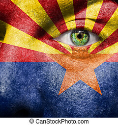 Flag painted on face with green eye to show Arizona support