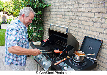 Retired dutch senior man grilling hamburgers in his back...