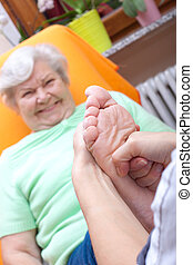 female Nurse massaging foot of a patient