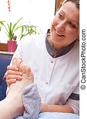 Nurse washes the feet of a patient