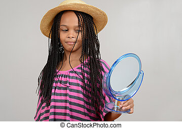 Young Black girl looking in mirror on grey background