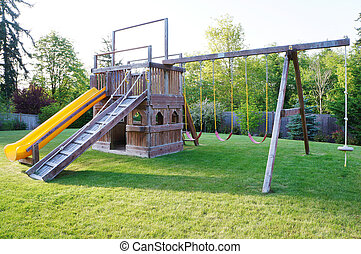 Kids playground in fenced back yard of house.