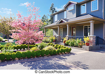 Grey large luxury house with spring blooming trees. - Grey...
