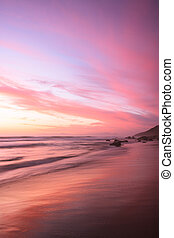 Pink sunset reflects on the beach