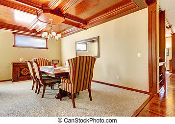 Dining room with yellow walls and wood ceiling.