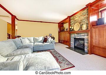 Large living room with sectional grey sofa and fireplace.