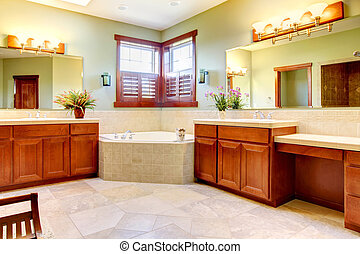 Large bathroom with double wood cabinets and corner tub.