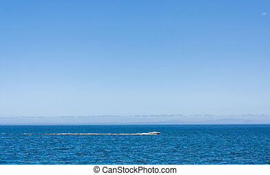 Tranquil water - A speedboat crosses the horizon