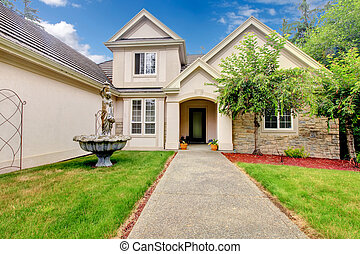 Large beautiful beige and grey house exterior during summer.