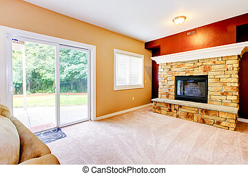 Empty Living room with large fireplace and door to backyard.