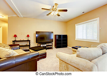 Living yellow room with brown sofas and TV. - Large yellow...