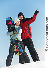 Happy sportswoman and sportsman with snowboard - smiley...