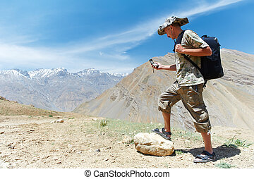 Tourist hiker with compass in mountains