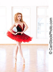 Gracefully, En-Pointe - Young ballerina in red tutu...