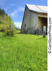 Old large shed with green spring landscape and fence. - Old...