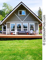 Modern American farm cottage house exterior with deck. -...