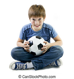 Boy sitting on floor with football ball - Twelve years old...