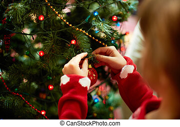 Decorating xmas tree - Close-up of child hanging decorative...