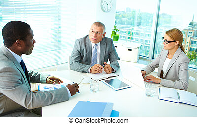 Meeting - Portrait of serious boss talking and his employees...