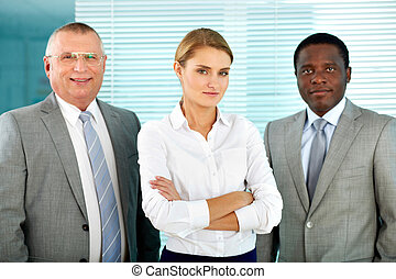 Partnership - Portrait of three business partners looking at...