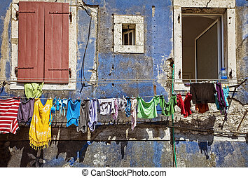 washing - clean clothing on a rope. blue wall with windows
