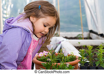 Curious - Little girl in greenhouse smelling a flower.