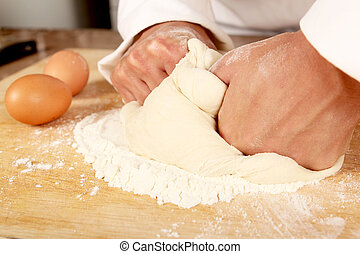 Baker kneading dough - Baker kneading pizza dough on a...