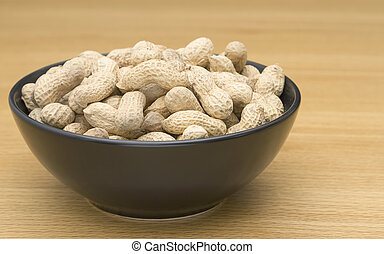 Peanuts in a black bowl on table