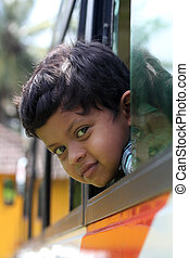 Handsome and cute little indian school kid looking back with...