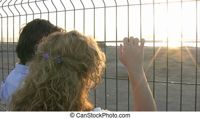 Mother and son standing at the fence