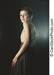 Retro styled fashion portrait of a young woman looking over the shoulder.