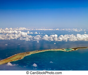 Polynesia. The atoll ring in ocean is visible through clouds. Aerial view.