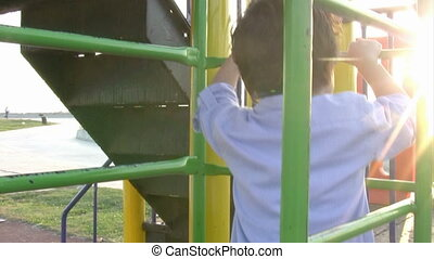 Little boy climbing bars at park