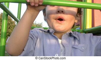 Little boy climbing bars at park