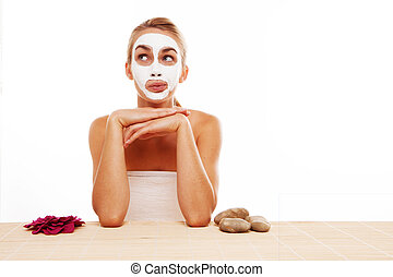 Woman sitting in a face mask at a table in a spa flanked by...