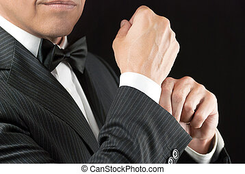 Man In Tux Fixes Cufflink - Close-up of a man in a tux...