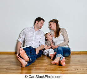 Happy family sitting on the floor against the wall
