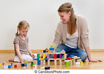 Cute little girl and young woman sitting on the floor and playing with building blocks