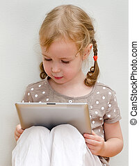 Cute little girl sitting against the wall and using tablet...