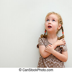 Portrait of little girl standing against the wall and...