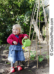 Little girl watering plants with watering pot - Little girl...