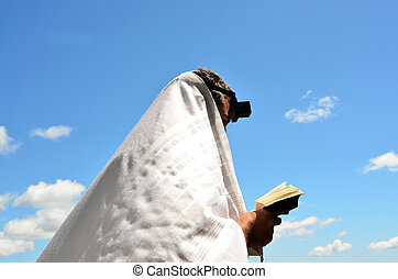 Jewish man pray to God under the open blue sky - A Jewish...