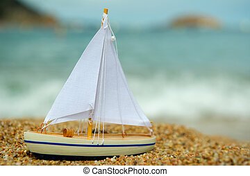 Toy saill boat at the beach