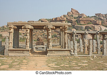indian temple ruin infront of massive rock boulders, hampi
