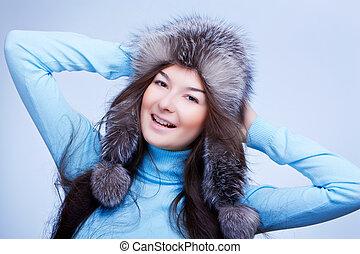 joyful woman in fur cap on blue background