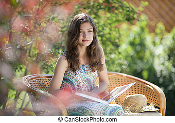Girl reading book sitting in wicker chair outdoor in summer...