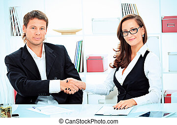 partnership - Business woman and businessman shaking hands...