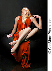 Woman in evening dress reclining on a chair on black...