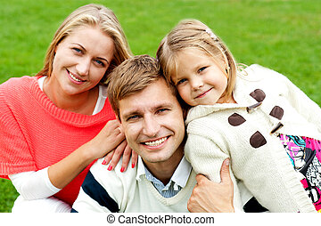 Joyous family of three. Loving and caring. Outdoor shot
